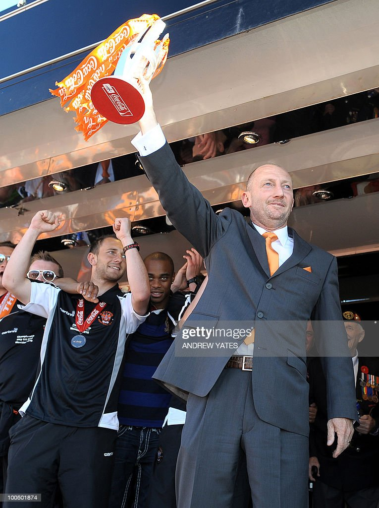 Blackpool football manager Ian Holloway (R) holds the playoff trophy at their promotion party in Blackpool, north west England, on May 24, 2010, after winning promotion to the Premier League by beating Cardiff.