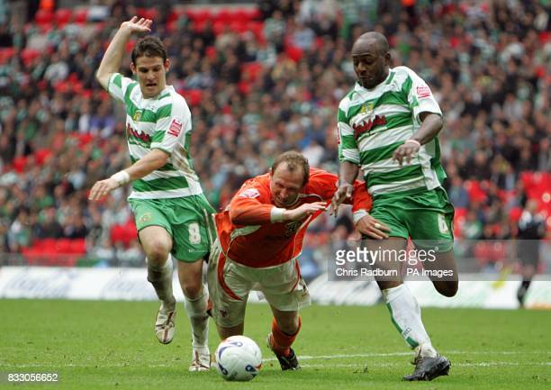 Blackpool's Andrew Morrell goes down under the challenge from Yeovil's Terrell Forbes and Anthony Barry