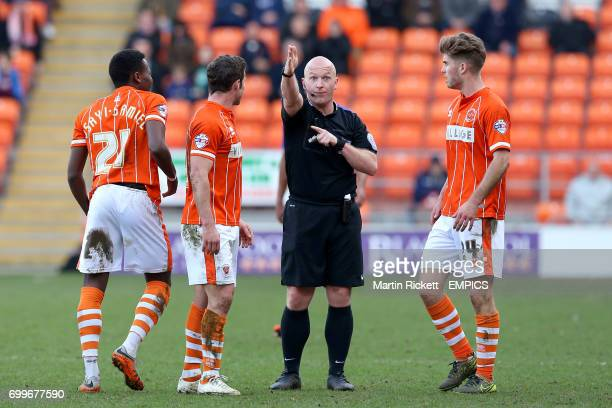 Blackpool's Bright OsayiSamuel David Norris and Luke Higham with referee Simon Hooper