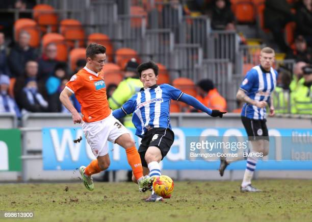 Blackpool's Dom Telford battles for the ball with Wigan Atheltic's Kim BoKyung