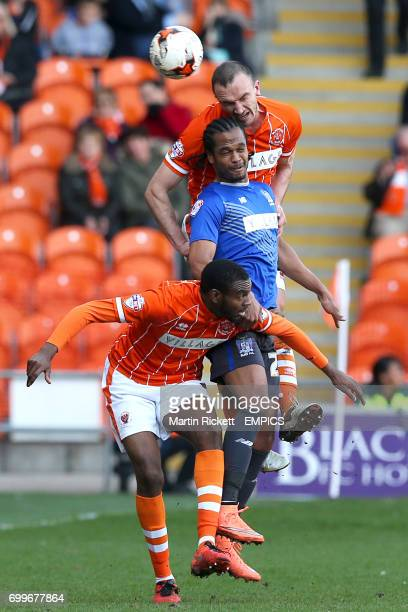 Blackpool's Hayden White and Tom Aldred battle for the ball in the air with Bury's Nathan Delfouneso