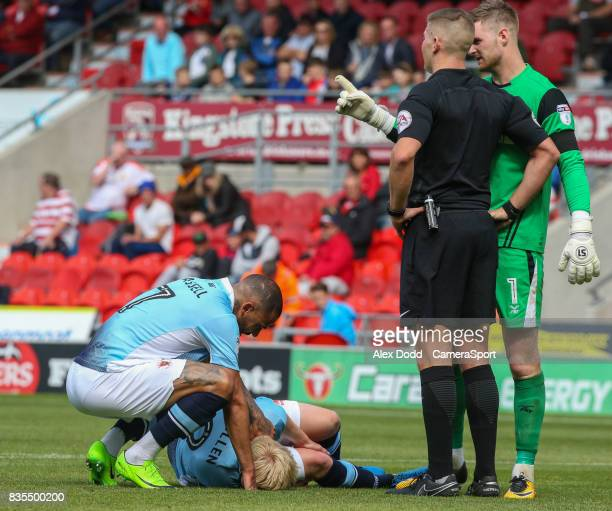 Blackpool's Kyle Vassell comforts Mark Cullen after he went down clutching his leg during the Sky Bet League One match between Doncaster Rovers and...