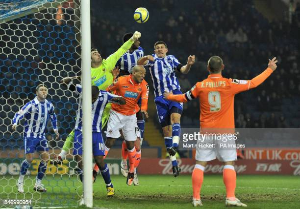 Blackpool's Matthew Gilks punches clear from Sheffield Wednesday's Reda Johnson and Danny Batth during the FA Cup Fourth Round Replay at Hillsborough...