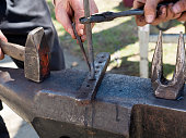Blacksmith forge with hammer iron on anvil. Detail of working hands. Daily sunshine
