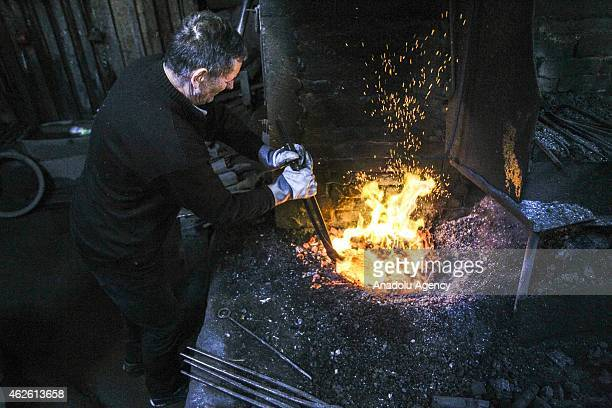 A blacksmith forges iron at a smithery in Ochevia village of Vares Bosnia and Herzegovina on January 31 2015 Smiths in Ochevia carry on forging...