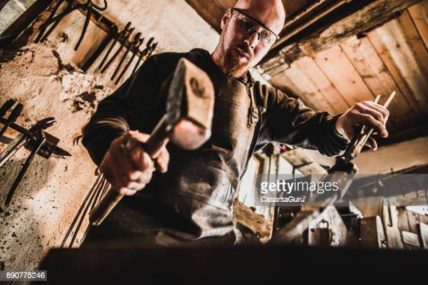 Blacksmith Holding a Hammer and Locking Pliers