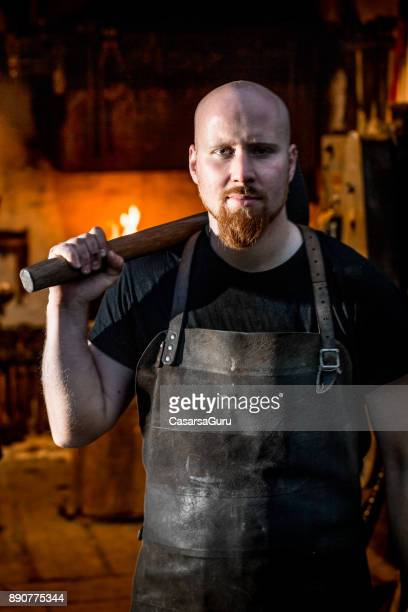 Blacksmith Holding a Hammer Over his Shoulders, Forge in the Background
