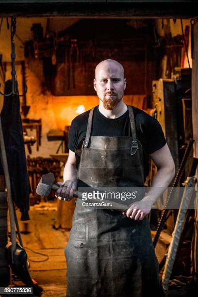 Blacksmith Holding a Sledge Hammer with Both Hands, Workshop in the Background