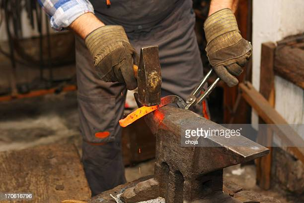 Blacksmith is hammering a red hot piece of iron