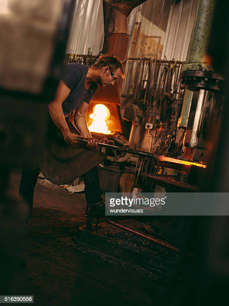 Blacksmith operating mechanical press in workshop