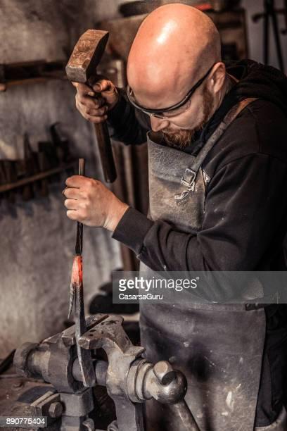 Blacksmith Shaping Iron Using Hammer and Spike