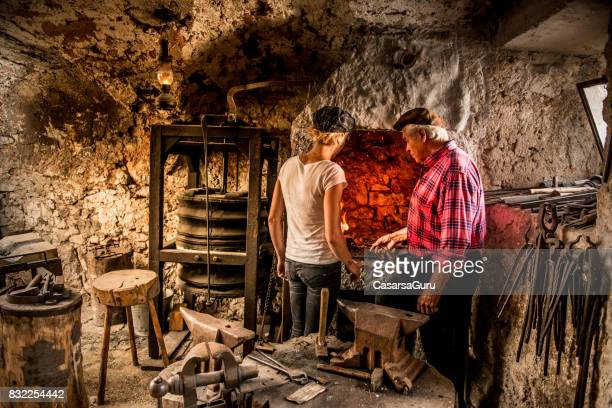 Blacksmith Showing to Young Woman how to Prepare a Fire