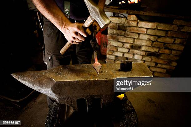 Blacksmith working with hammer at anvil