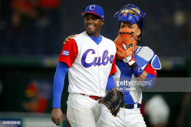 Bladimir Banos and Frank Morejon of Team Cuba smile as they walk back to the dugout during Game 2 of Pool B against Team China at the Tokyo Dome on...
