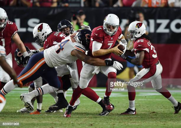 Blaine Gabbert of the Arizona Cardinals runs with the ball while being tackled from behind by Roy RobertsonHarris of the Chicago Bears during the...