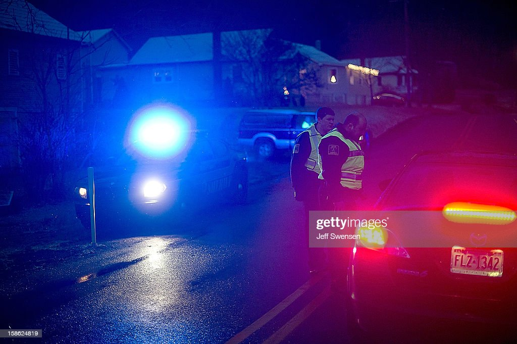 Blair County Sheriffs Deputies stand at the road block in Blair County on December 21, 2012 in Frankstown Township, Pennsylvania. According to reports, a man shot and killed two men and one woman and injured three state troopers before being shot and killed by police along Juniata Valley Road in Frankstown Township.