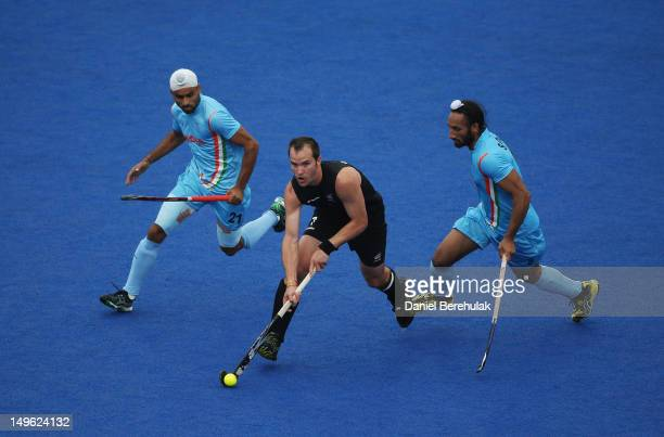 Blair Hopping of New Zealand is challenged by Gurwinder Singh Chandi and Sardar Singh of India during the Men's preliminary Hockey match on Day 5 of...