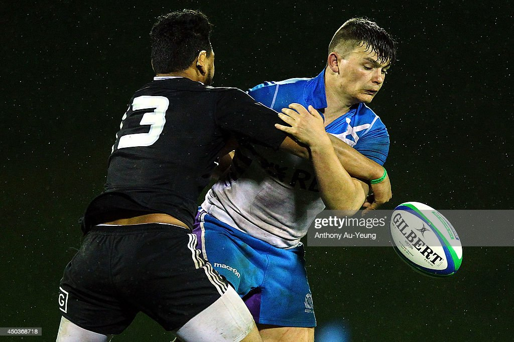 Blair Hutchison of Scotland loses the ball in the tackle from TJ Faiane of New Zealand during the 2014 Junior World Championship match between New Zealand and Scotland at ECOLight Stadium, Pukekohe on June 10, 2014 in Auckland, New Zealand.