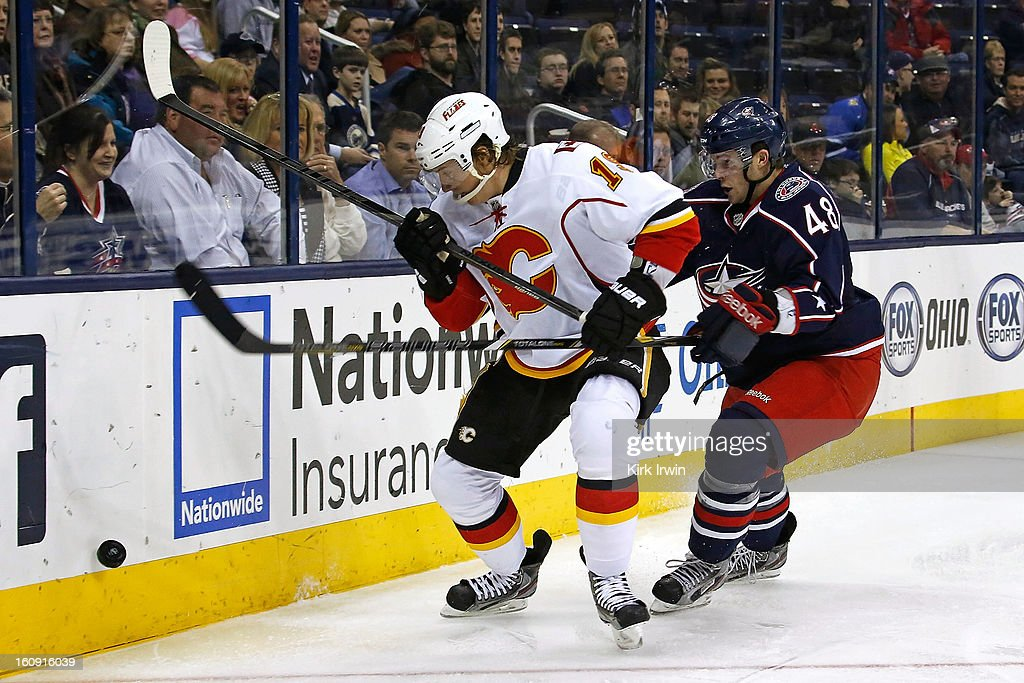 Blair Jones #19 of the Calgary Flames and Cody Goloubef #48 of the Columbus Blue Jackets battle for control of a loose puck during the third period on February 7, 2013 at Nationwide Arena in Columbus, Ohio. Calgary defeated Columbus 4-3 in overtime.
