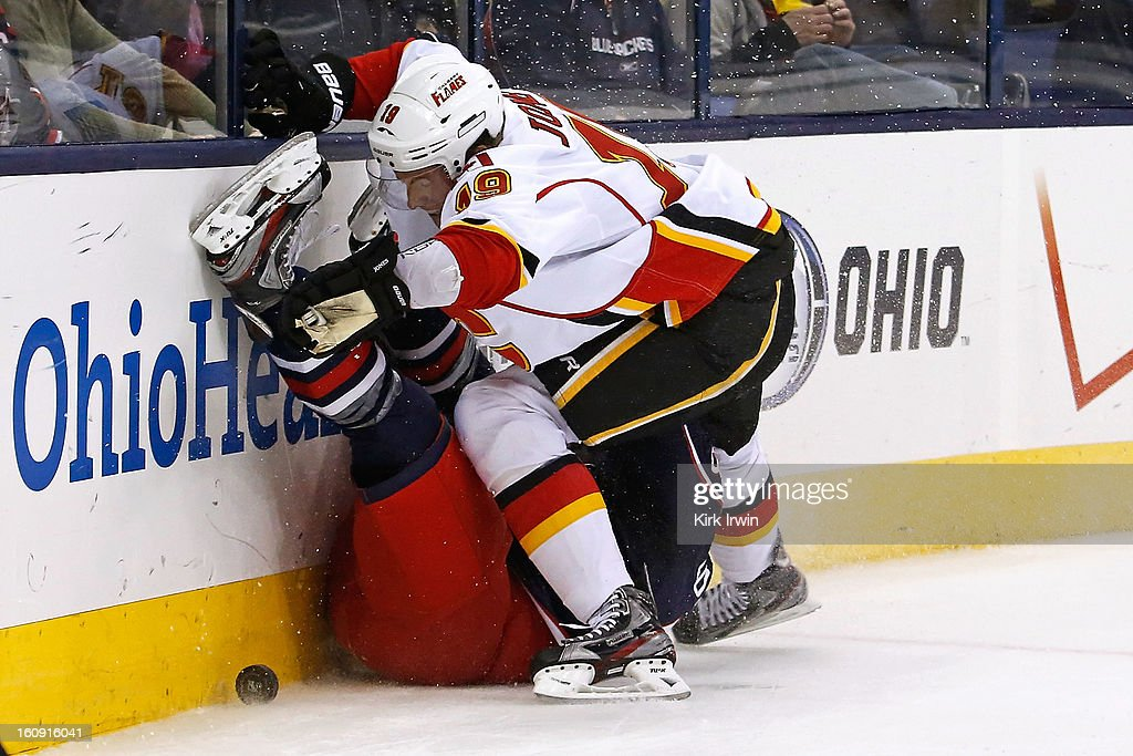 Blair Jones #19 of the Calgary Flames knocks Cody Goloubef #48 of the Columbus Blue Jackets onto the ice while chasing down a puck during the third period on February 7, 2013 at Nationwide Arena in Columbus, Ohio.