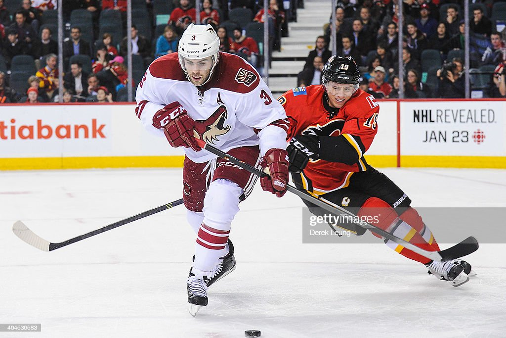 Blair Jones #19 of the Calgary Flames tries to check <a gi-track='captionPersonalityLinkClicked' href=/galleries/search?phrase=Keith+Yandle&family=editorial&specificpeople=606912 ng-click='$event.stopPropagation()'>Keith Yandle</a> #3 of the Phoenix Coyotes during an NHL game at Scotiabank Saddledome on January 22, 2014 in Calgary, Alberta, Canada.