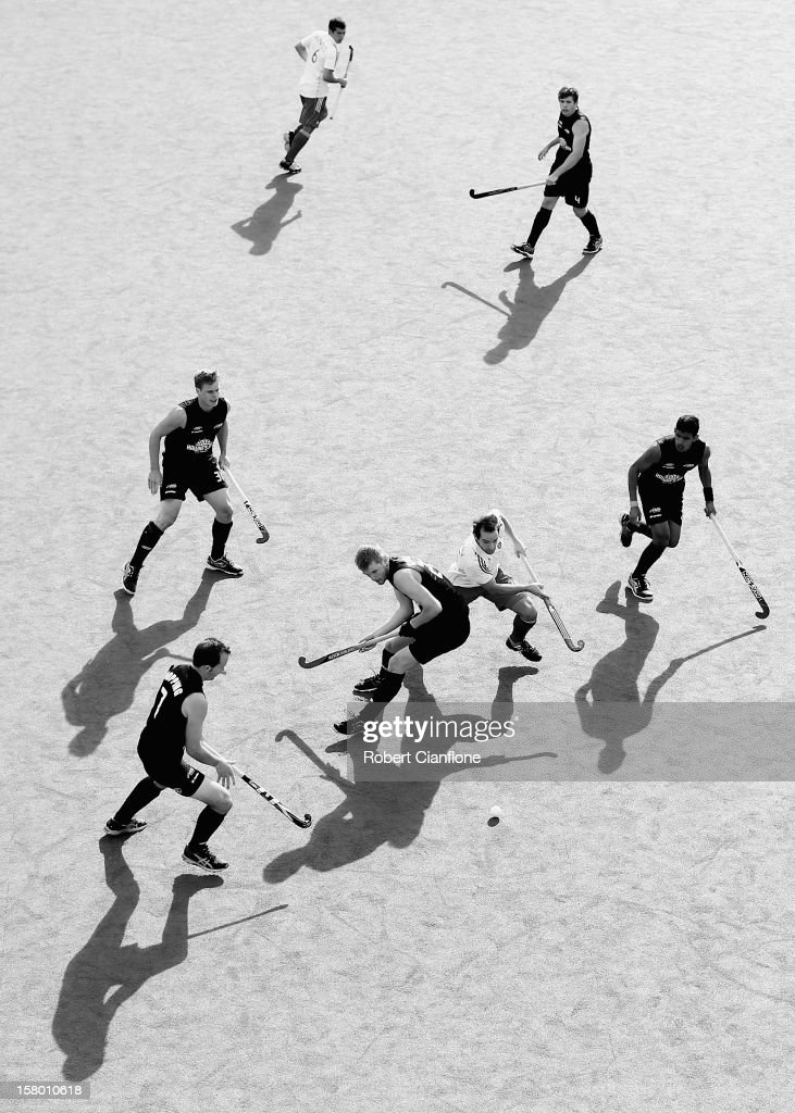 Blair Tarrant of New Zealand is challenged for the ball by Nick Catlin of England in the match between England and New Zealand during day six of the 2012 Champions Trophy at State Netball Hockey Centre on December 9, 2012 in Melbourne, Australia.