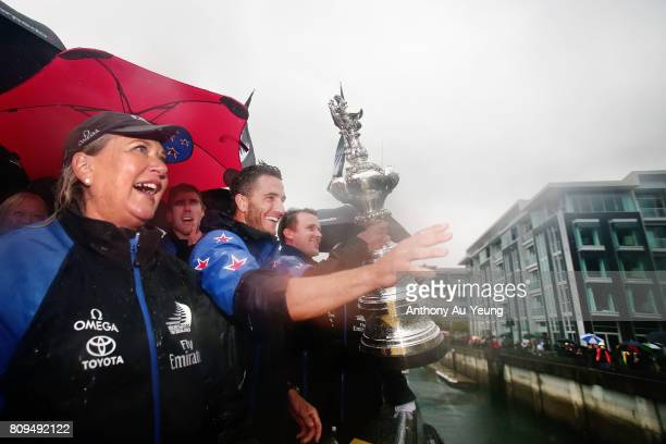 Blair Tuke cyclist/foil trimmer of Emirates Team New Zealand showcases the America's Cup trophy to the supporters during the Team New Zealand...