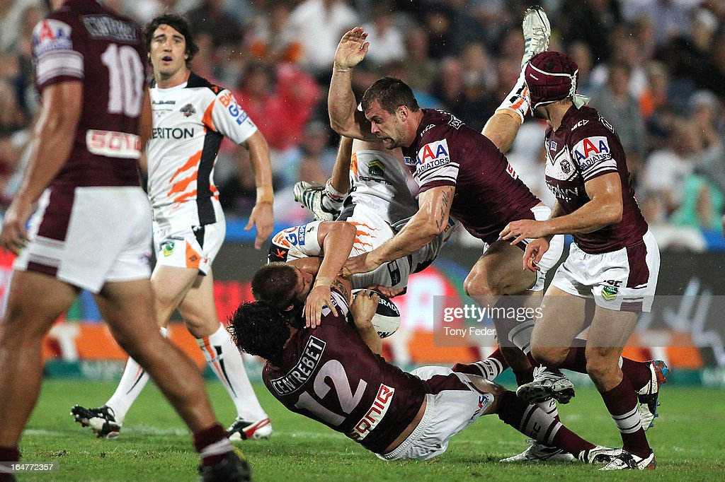 Blake Ashford of the Wests Tigers is tackled by Justin Horo and Brenton Lawrence of the Sea Eagles during the round four NRL match between the Manly Sea Eagles and the Wests Tigers at Bluetongue Stadium on March 28, 2013 in Gosford, Australia.