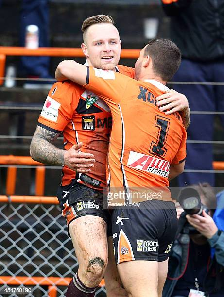 Blake Austin celebrates his try with team mate Jy Hitchcox during the round 26 NRL match between the Wests Tigers and the Cronulla Sharks at...