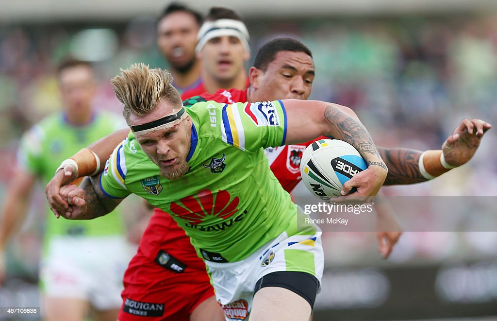 Blake Austin of the Raiders fends off the tackle of Tyson Frizell during the round three NRL match between the Canberra Raiders and the St George...