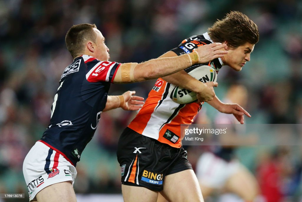 Blake Aysford of the Tigers is tackled by James Maloney of the Roosters during the round 23 NRL match between the Wests Tigers and the Sydney Roosters at Allianz Stadium on August 19, 2013 in Sydney, Australia.