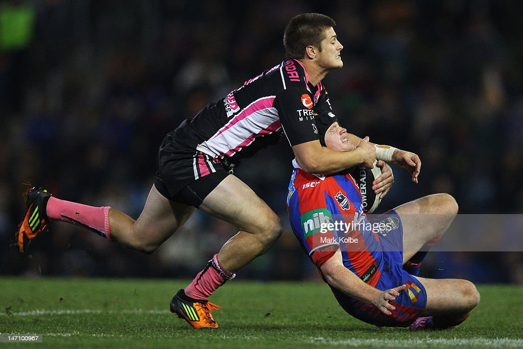 Blake Ayshford of the Tigers tackles Joel Edwards of the Knights during the round 16 NRL match between the Newcastle Knights and the Wests Tigers at Hunter Stadium on June 25, 2012 in Newcastle, Australia.