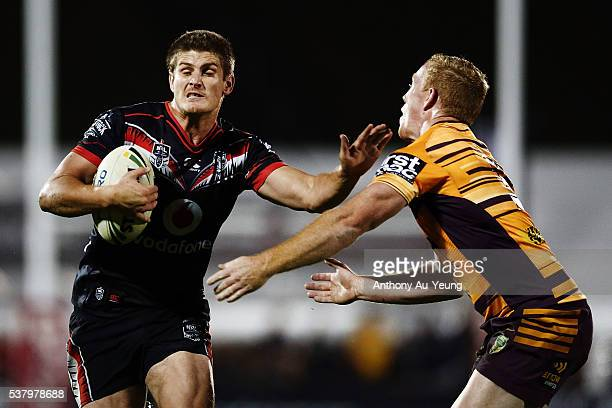 Blake Ayshford of the Warriors fends against Jack Reed of the Broncos during the round 13 NRL match between the New Zealand Warriors and the Brisbane...