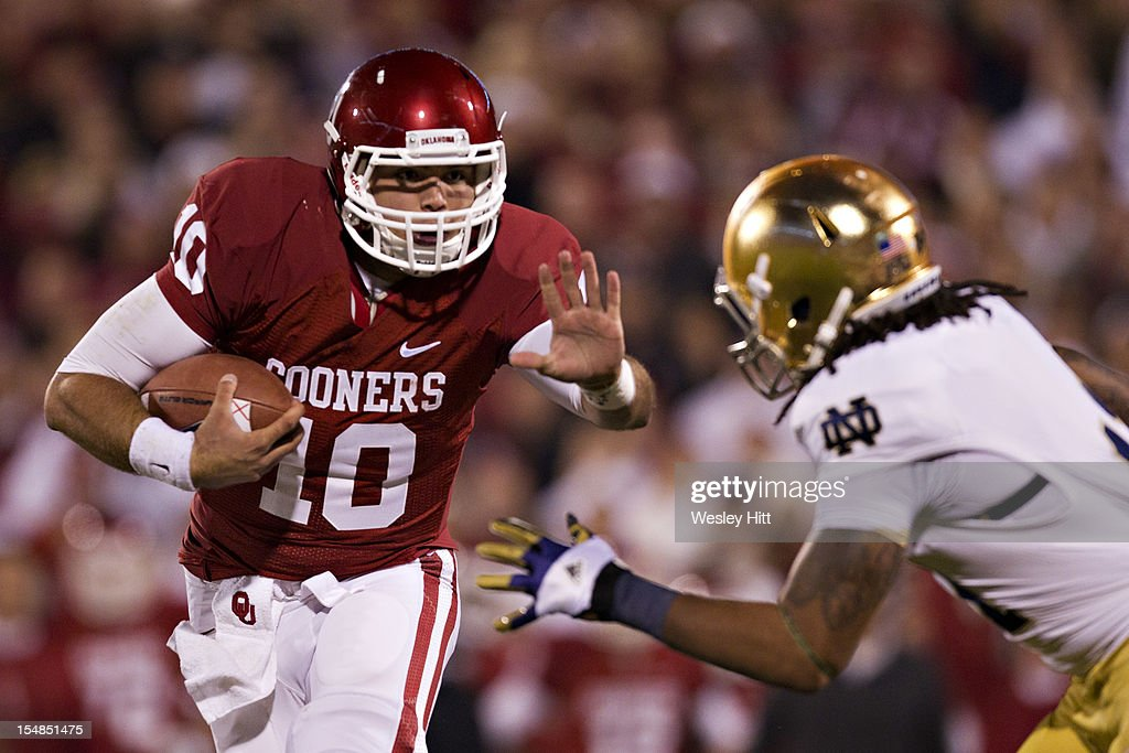 Blake Bell #10 of the Oklahoma Sooners avoids the tackle of Ishaq Williams #11 of the Notre Dame Fighting Irish on his way to a touchdown at Gaylord Family Oklahoma Memorial Stadium on October 27, 2012 in Norman, Oklahoma. The Fighting Irish defeated the Sooners 30-13.
