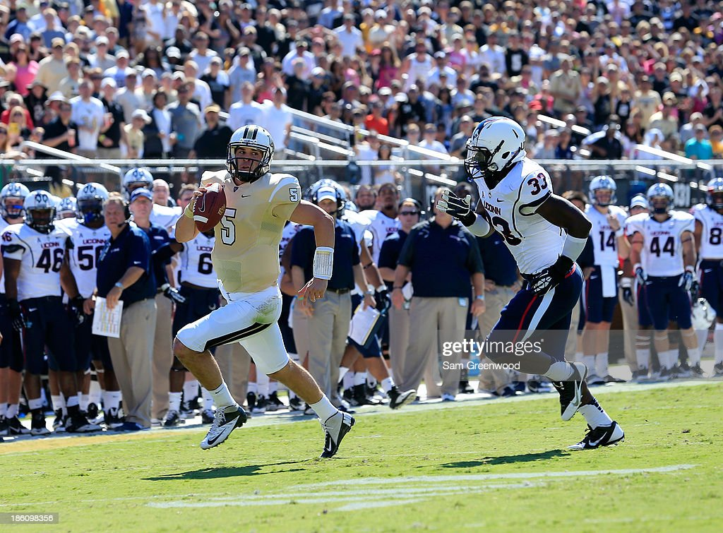Blake Bortles #5 of the UCF Knights runs past Yawin Smallwood #33 of the Connecticut Huskies during the game at Bright House Networks Stadium on October 26, 2013 in Orlando, Florida.