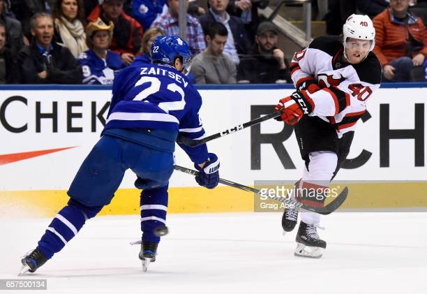 Blake Coleman of the New Jersey Devils shoots past Nikita Zaitsev of the Toronto Maple Leafs during the third period at the Air Canada Centre on...