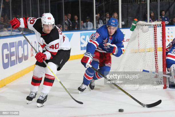 Blake Coleman of the New Jersey Devils skates with the puck against Brady Skjei of the New York Rangers at Madison Square Garden on December 9 2017...