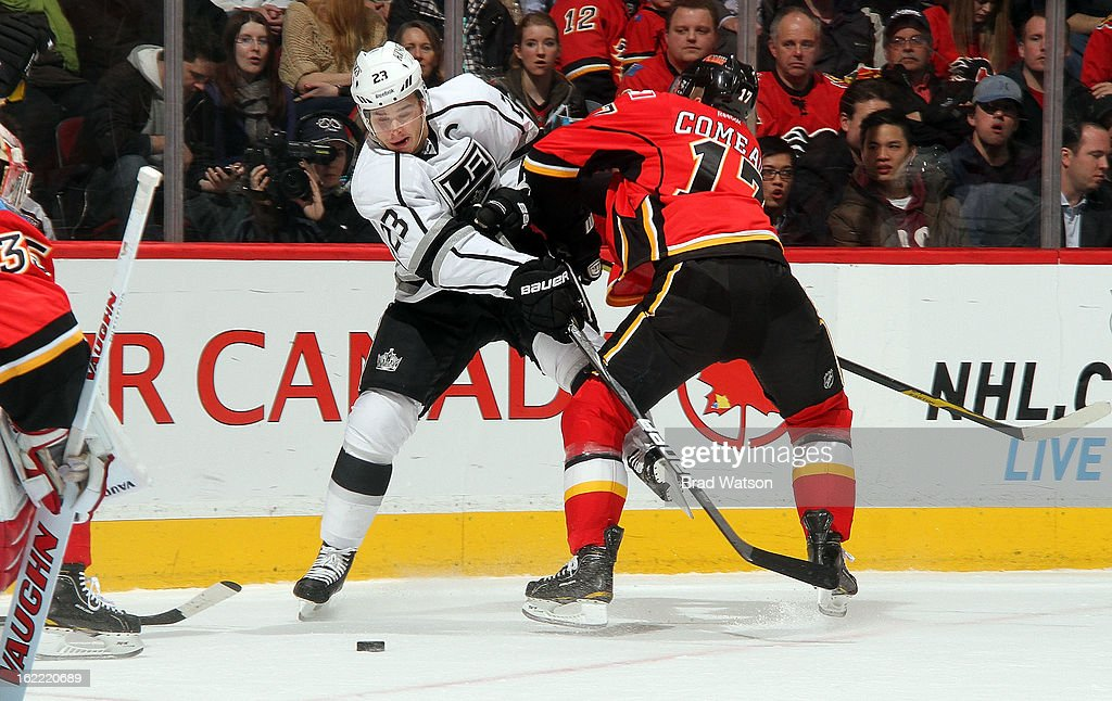 Blake Comeau #17 of the Calgary Flames checks Dustin Brown #23 of the Los Angeles Kings on February 20, 2013 at the Scotiabank Saddledome in Calgary, Alberta, Canada.