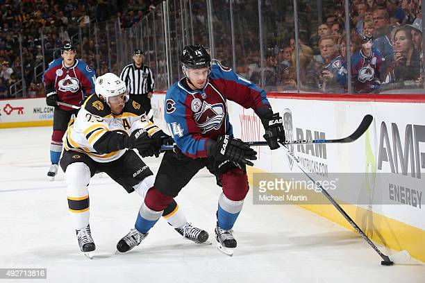 Blake Comeau of the Colorado Avalanche skates with the puck as Chris Kelly of the Boston Bruins defends at the Pepsi Center on October 14 2015 in...