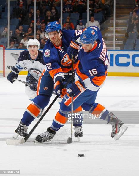 Blake Comeau of the New York Islanders collides with teammate Marty Reasoner while in pursuit of a loose puck at Nassau Veterans Memorial Coliseum on...