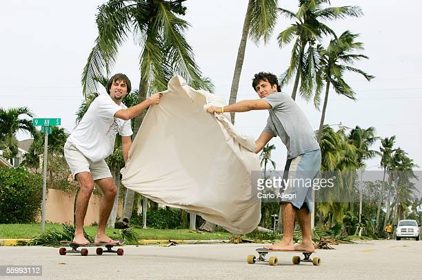 Blake Crawford and Carlos Galceran take advantage of the heavy winds and use a bed sheet as a sail as they skateboard down a steet as Hurricane Wilma...