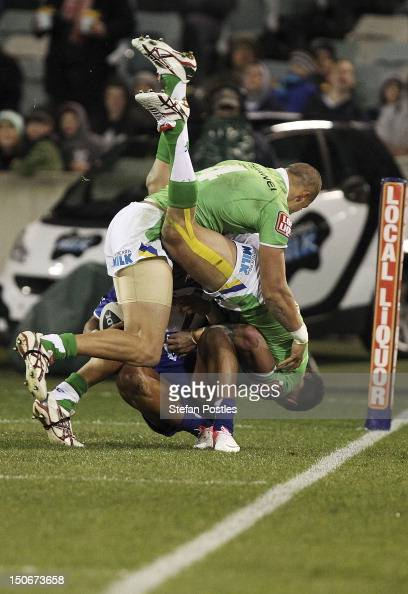 Blake Ferguson and Sandor Earl of the Raiders force Ben Barba of the Bulldogs to the sideline during the round 25 NRL match between the Canberra...