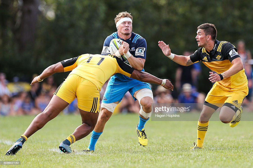 Blake Gibson of the Blues is tackled by <a gi-track='captionPersonalityLinkClicked' href=/galleries/search?phrase=Julian+Savea&family=editorial&specificpeople=5780264 ng-click='$event.stopPropagation()'>Julian Savea</a> and Otere Black of the Hurricanes during the Super Rugby pre-season match between the Blues and the Hurricanes at Eketahuna Rugby Club on February 13, 2016 in Eketahuna, New Zealand.
