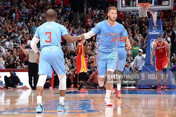 Blake Griffin high fives teammate Chris Paul of the Los Angeles Clippers during the game against the Houston Rockets on March 15 2015 at STAPLES...