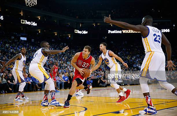 Blake Griffin of the Los Angeles Clippers dribbles between Festus Ezeli and Stephen Curry of the Golden State Warriors at ORACLE Arena on November 4...