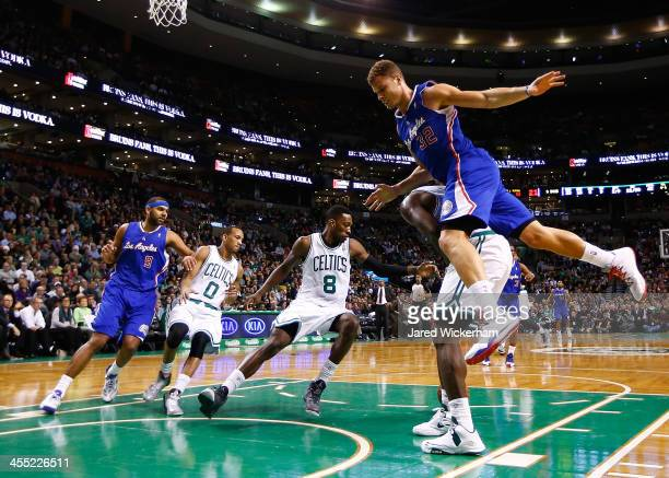 Blake Griffin of the Los Angeles Clippers jumps on the back of Brandon Bass of the Boston Celtics in the second half during the game at TD Garden on...