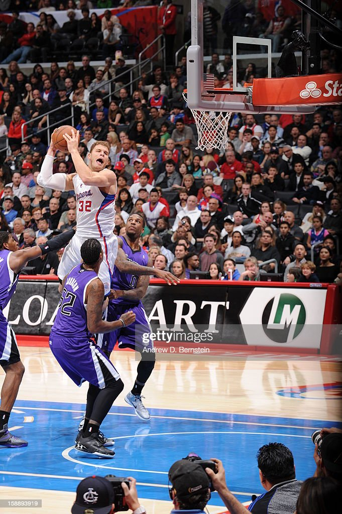 Blake Griffin #32 of the Los Angeles Clippers rises for a dunk against James Johnson #52 and Thomas Robinson #0 of the Sacramento Kings at Staples Center on December 21, 2012 in Los Angeles, California.