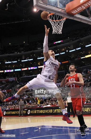 Blake Griffin of the Los Angeles Clippers shoots over Zaza Pachulia of the Atlanta Hawks at Staples Center on March 14 2012 in Los Angeles California...