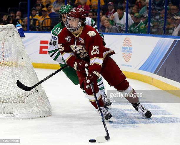 Blake Hillman of the Denver Pioneers wraps around the net as Austin Poganski of the North Dakota Fighting Hawks defends during semifinals of the 2016...
