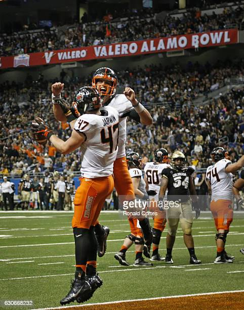 Blake Jarwin of the Oklahoma State Cowboys celebrates his touchdown reception against the Colorado Buffaloes with Mason Rudolph of the Oklahoma State...